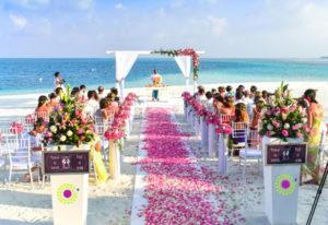 beach wedding with fushia petals and white chairs