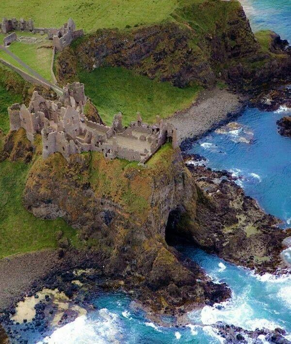 view from above Dunluce castle in Ireland of opening to mermaid cave