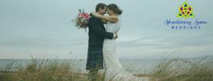 bride and groom in kilt on beach with ocean behind them