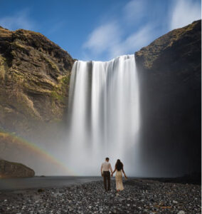 bride and groom walking toward a large waterfall with rainbow