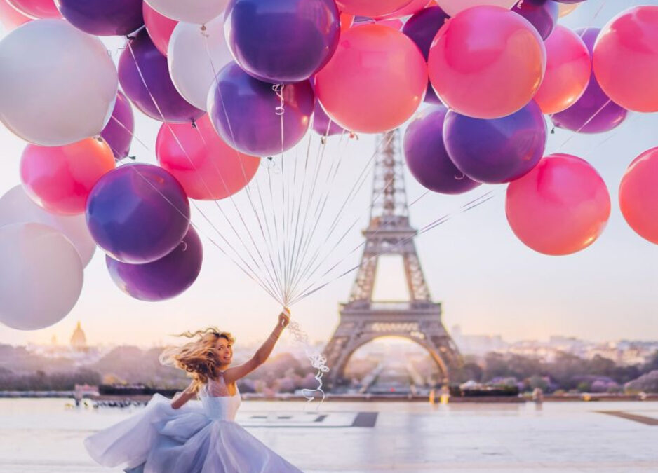 girl in dress with large amount of pink and purple balloons in Paris, France with eiffel tower in background